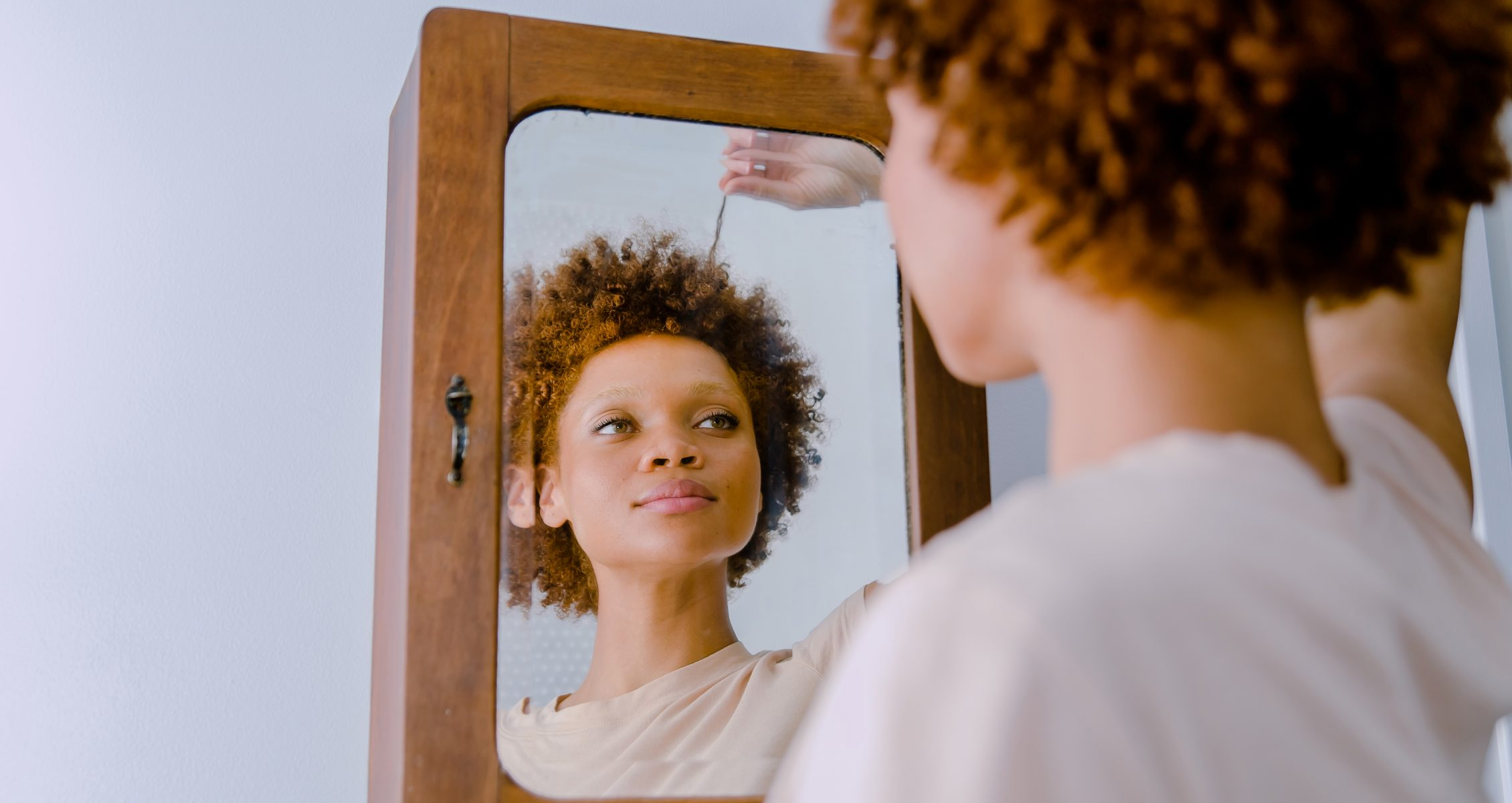 Curly haired woman staring at her reflection in the mirror examining her hair while pulling on one of her strands