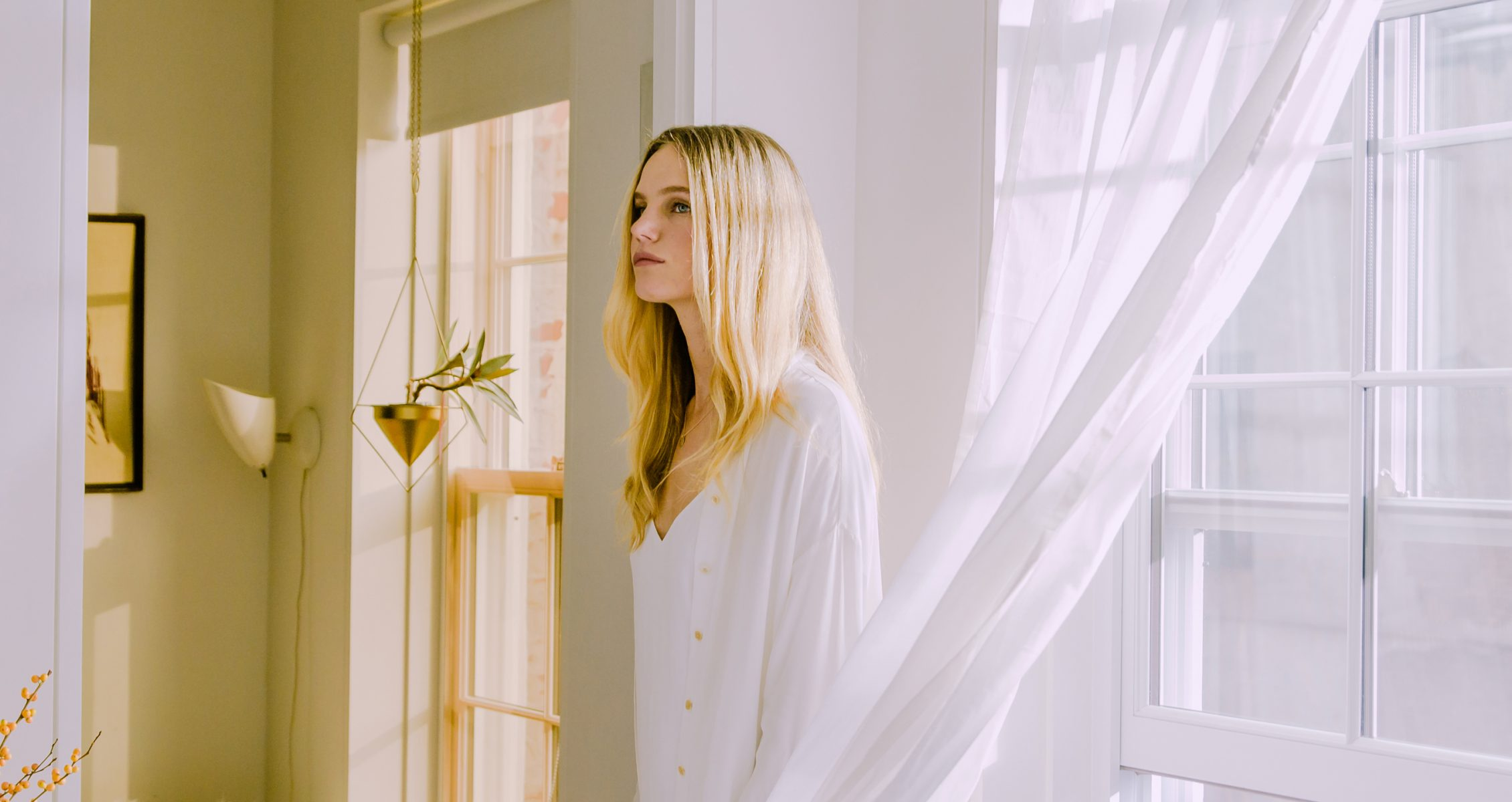 Blonde woman standing in her living room in front of a bright open window