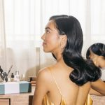 a woman with dark, sleek hair sits at her vanity in a yellow, silk slip dress