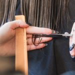 The hands of a woman cutting someones hair with a comb in one had and scissors in the other