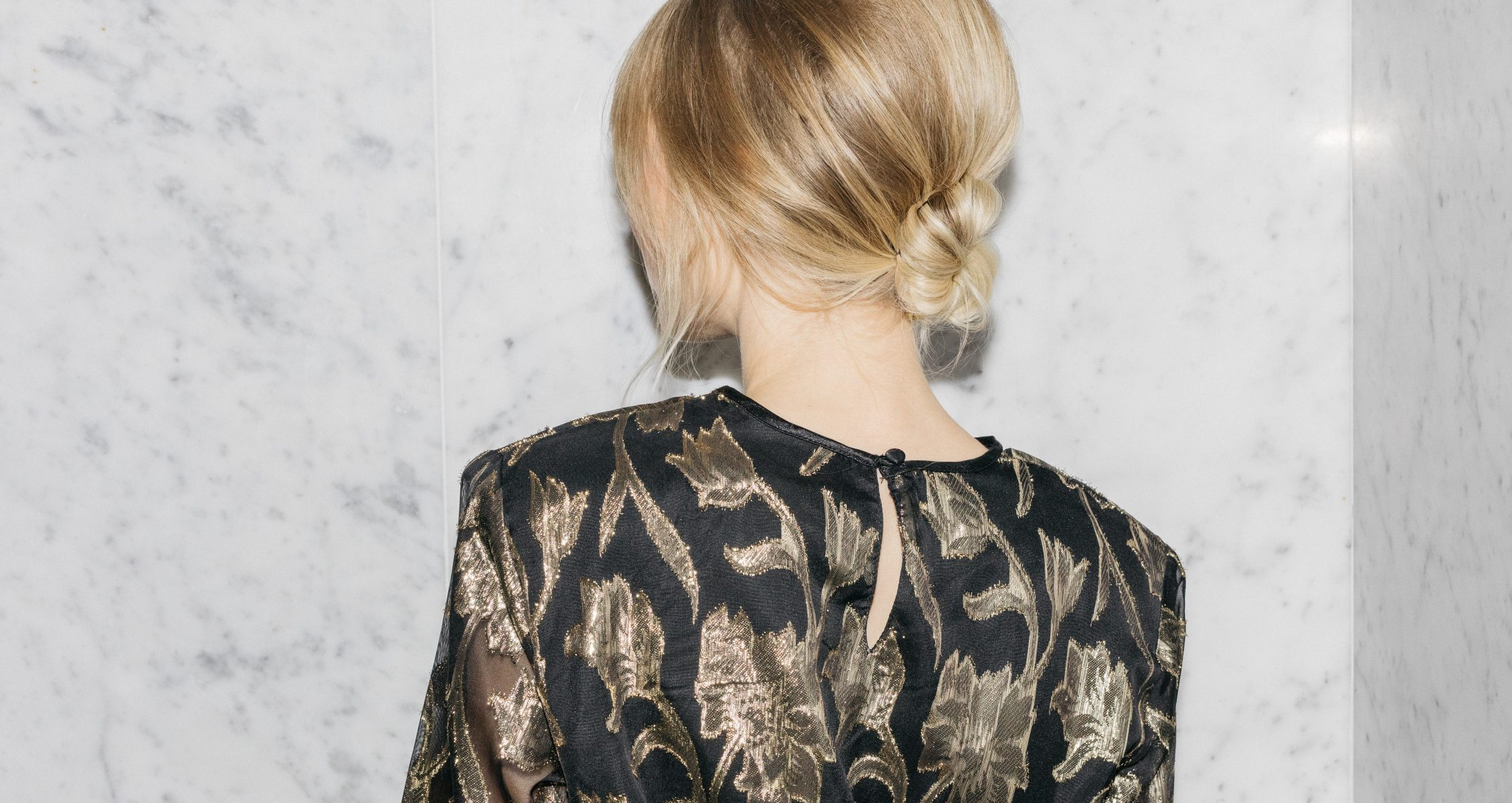 woman with blonde hair in a low bun has her back to the camera and poses on a marble background with a gold and black dress on