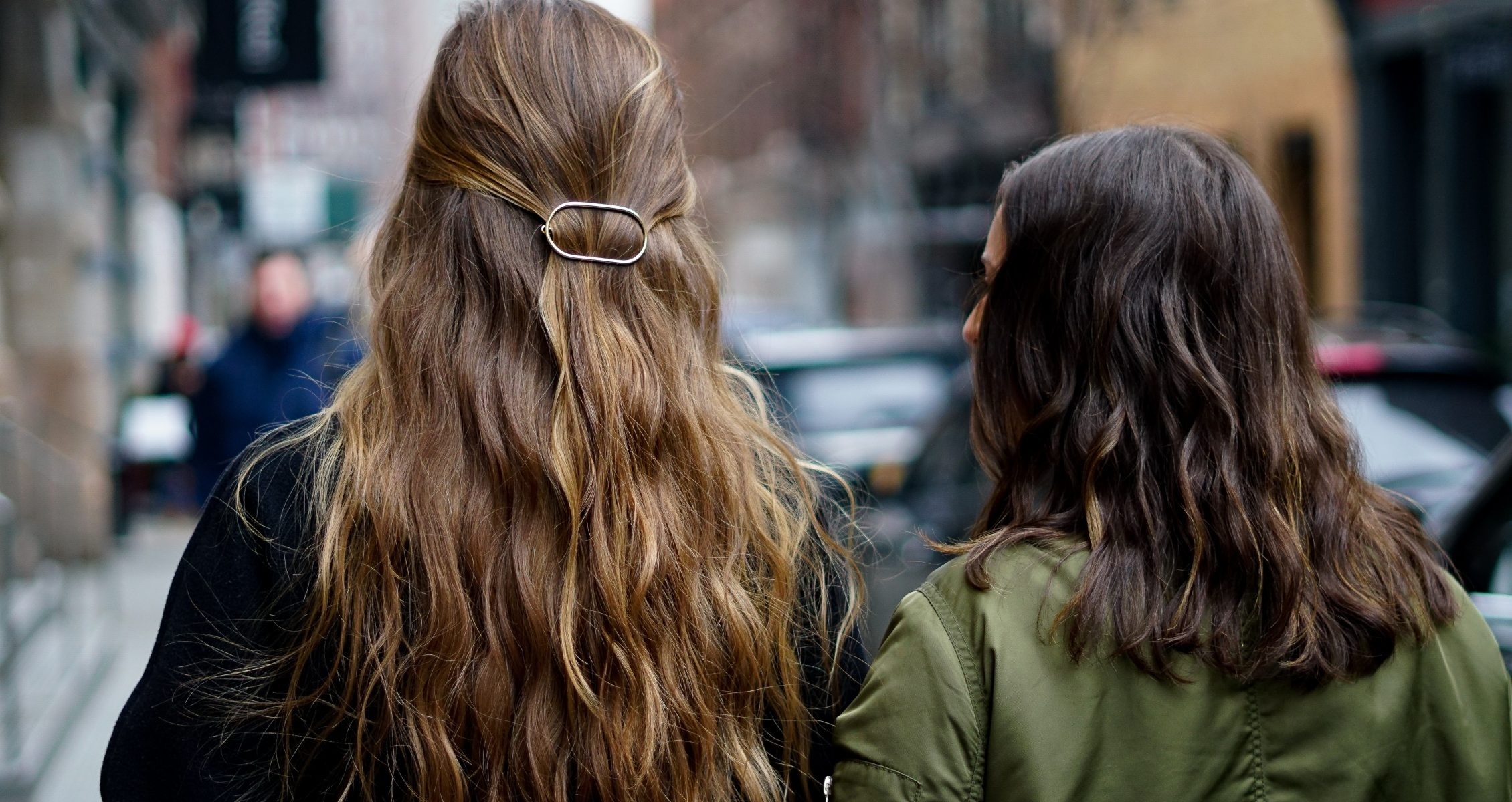 two women walk down an NYC street on a winter day with their backs faced to the camera and jackets on