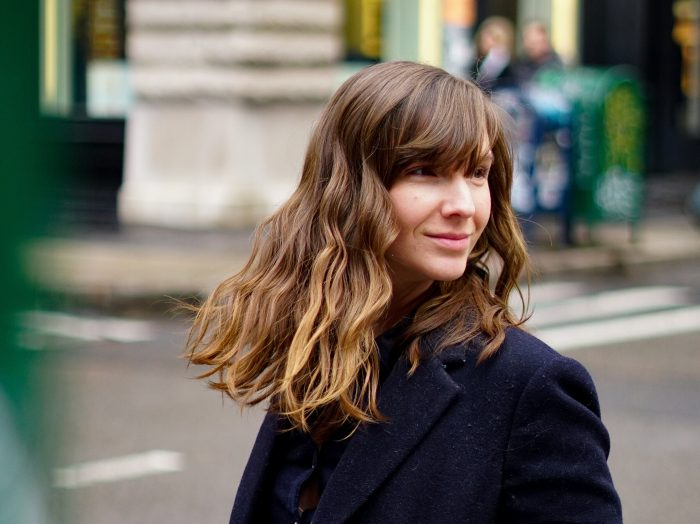 woman with wavy brown hair and bangs stands on a busy NYC street and smiles