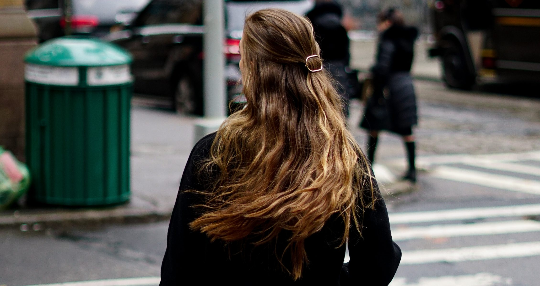 a woman with very long honey blonde hair stands in a busy NYC street wearing a black coat