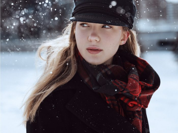 Blonde woman standing out in the snow wearing a black hat, black coat, and red plaid scarf.