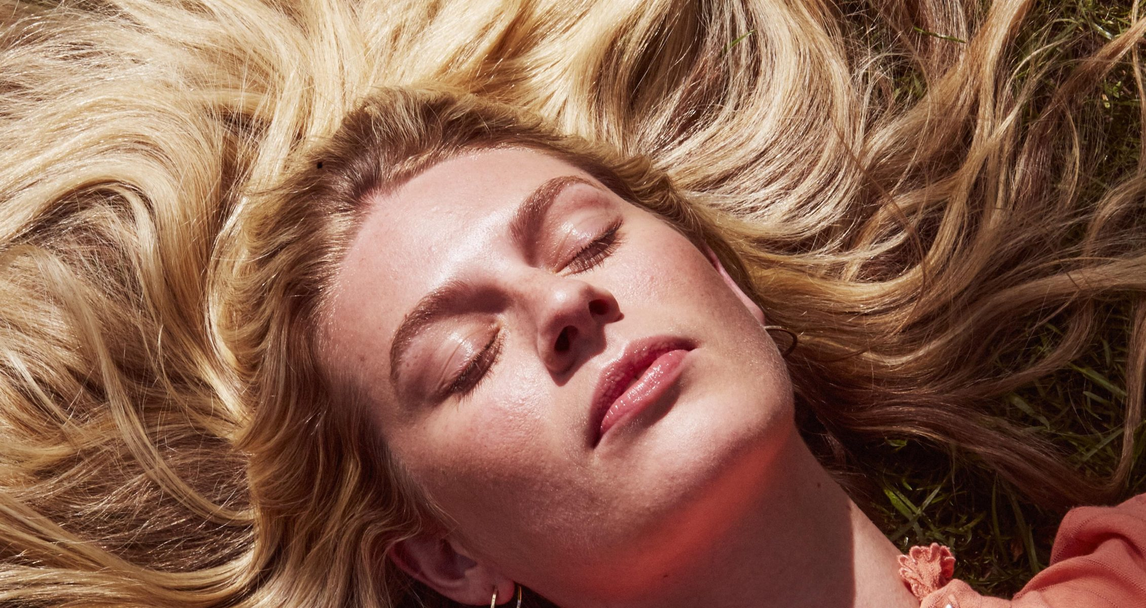 Prose model with shiny, long, blonde hair laying down with her eyes closed and her hair spread out around her