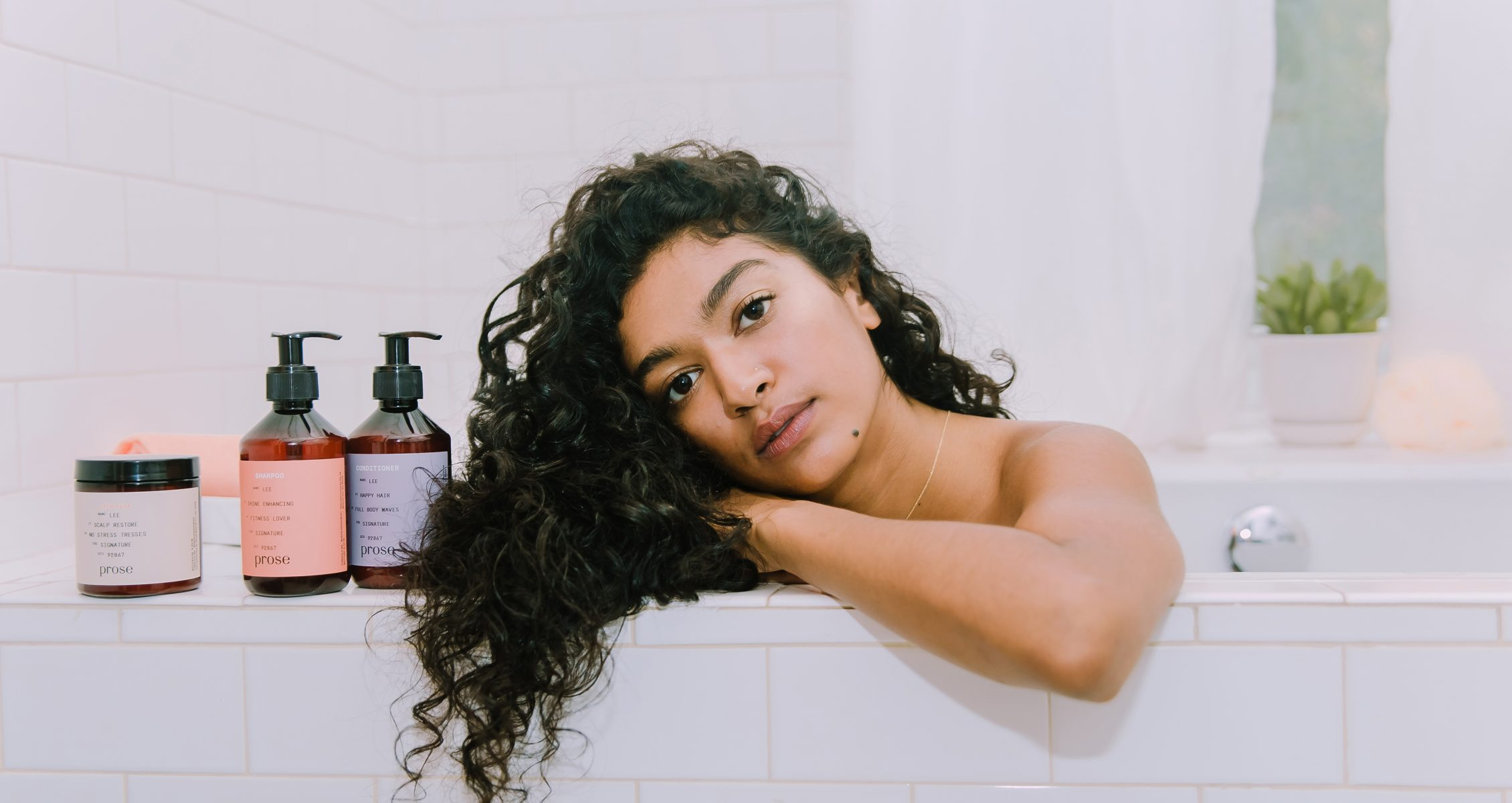 Woman with brown, curly hair in the bathtub with her Prose products