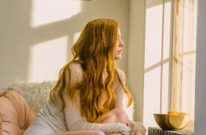 Prose model with long, red, wavy hair looking out a window with soft sunlight flooding in