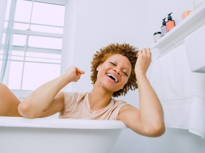 Prose model with short, curly, red hair laughing in a bathtub with her Prose products behind her