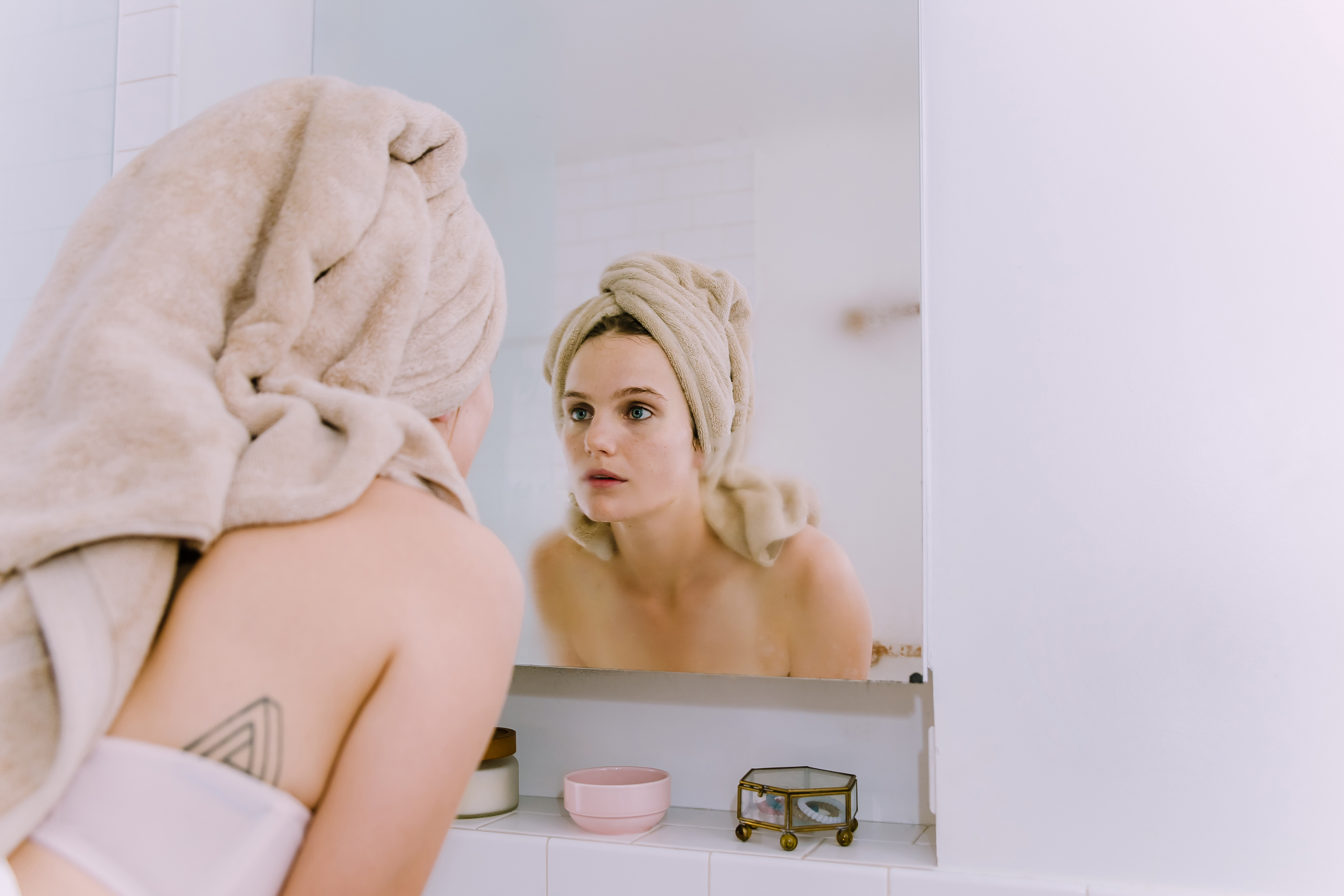 Prose model looking at herself in the bathroom mirror with a towel wrapped on top of her head