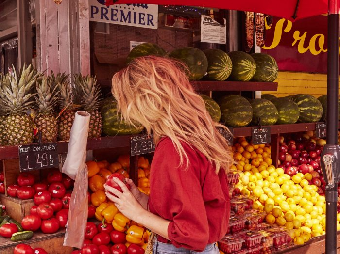 Prose model with long, blonde hair shopping in a red top at a fruit stand