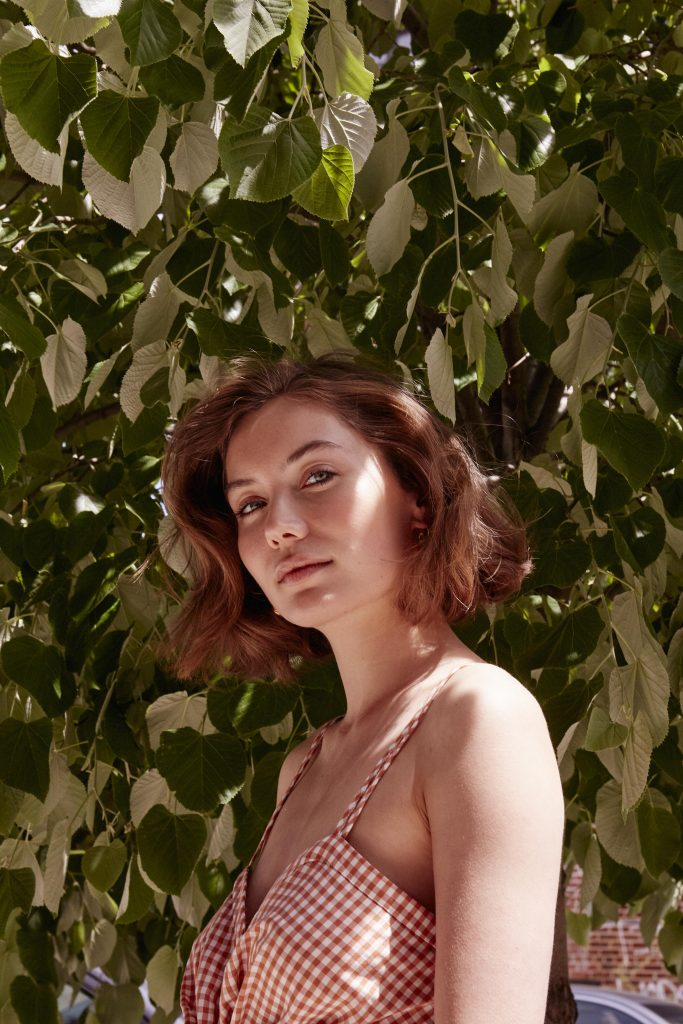 Prose model with short, brown hair posing in front of leafy tree in a red and white dress