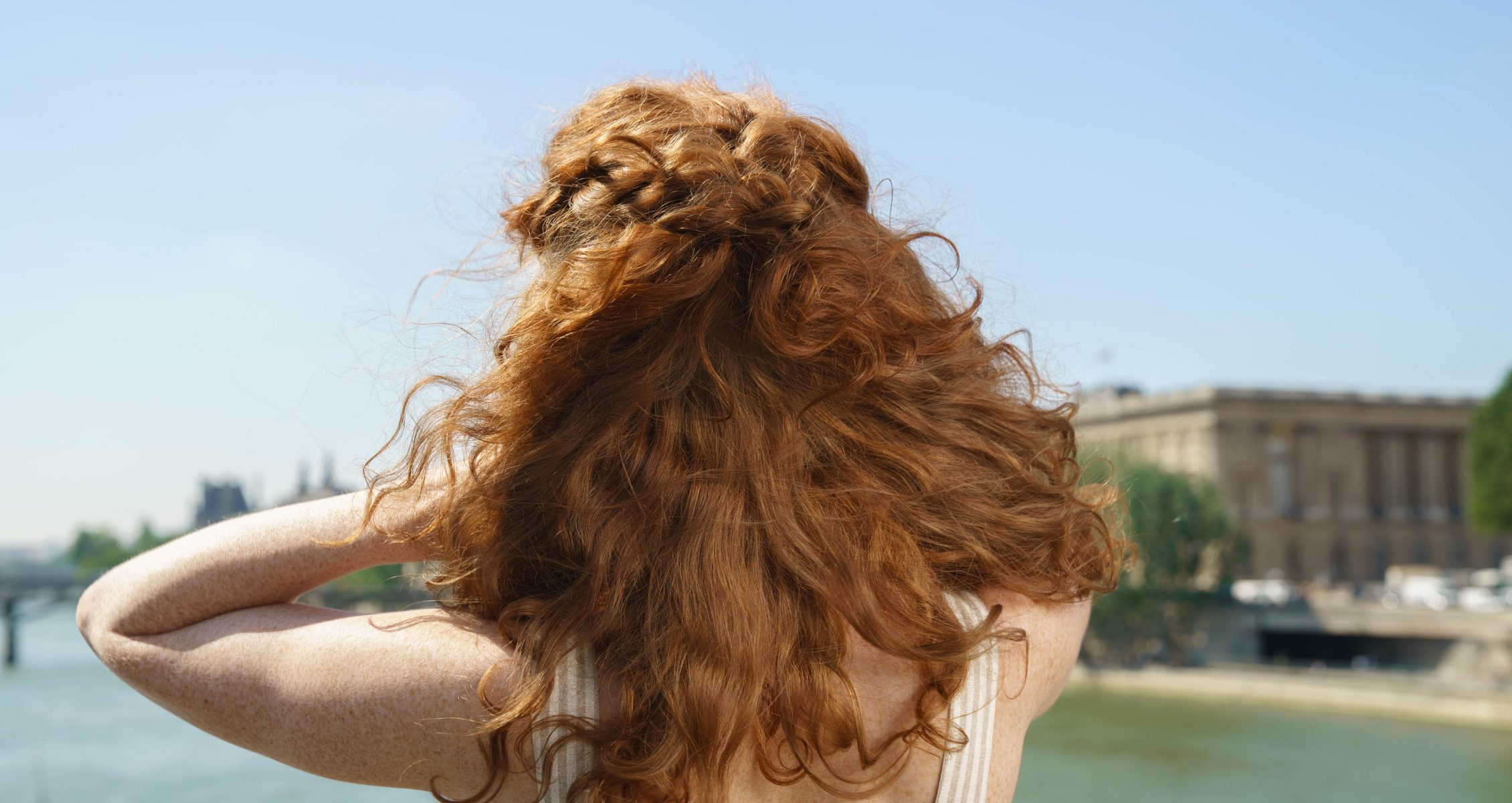 Prose model with red, wavy hair with her back to the camera and her hair blowing in the breeze