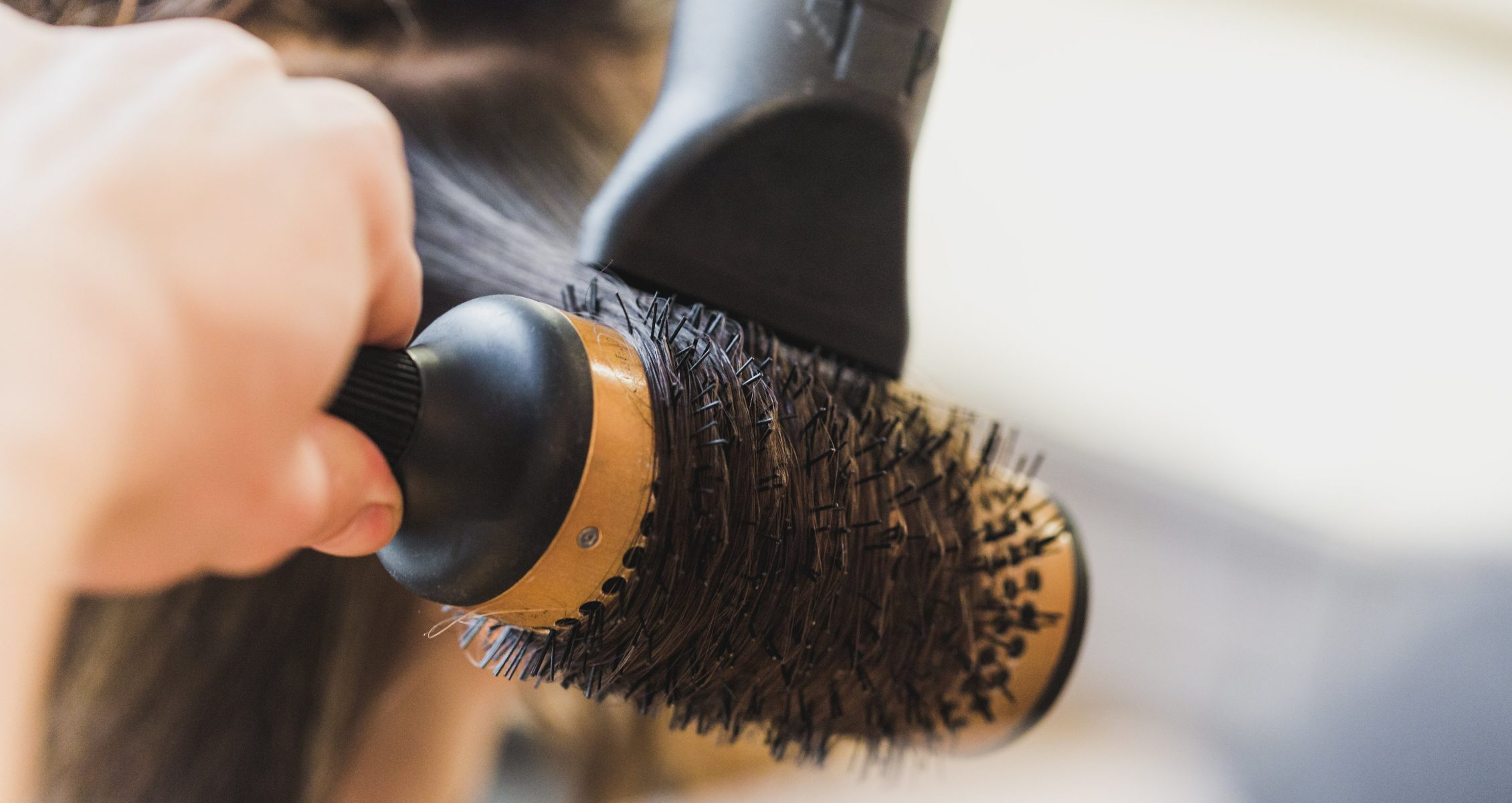 Brown hair being styled with a round brush and blow dryer