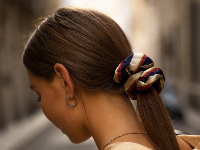 Girl with a long straight ponytail looks down with a striped scrunchie in her hair
