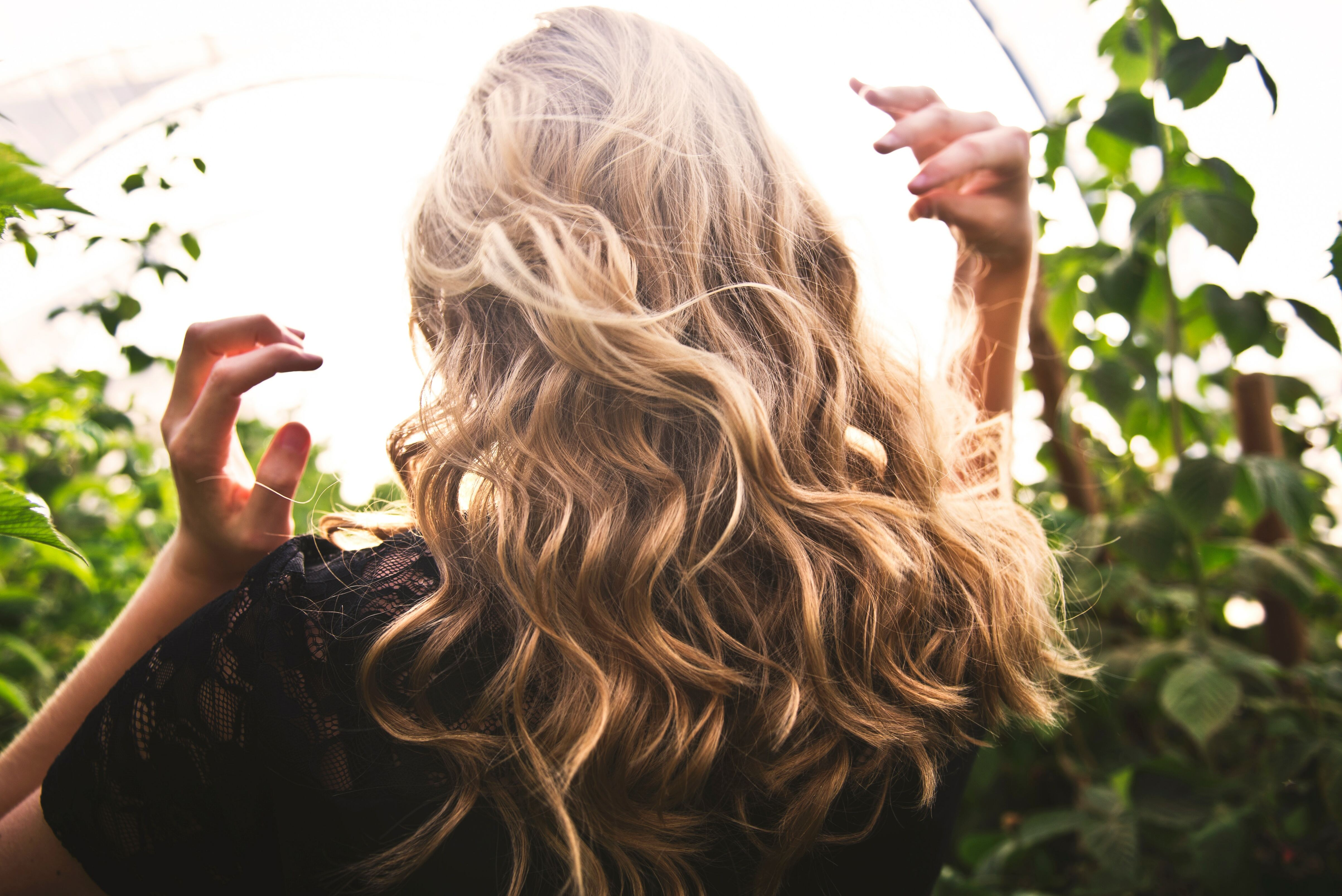 Back of woman's head with blonde hair surrounded by greenery