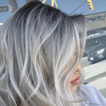 Woman with silver hair posing after a haircut