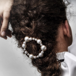 Pearl hair barrette featured in a curly, brunette braid