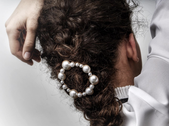 Pearl hair barrette featured in a curly, brunette braid
