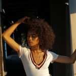 Woman with curly hair in sunlight touching her hair