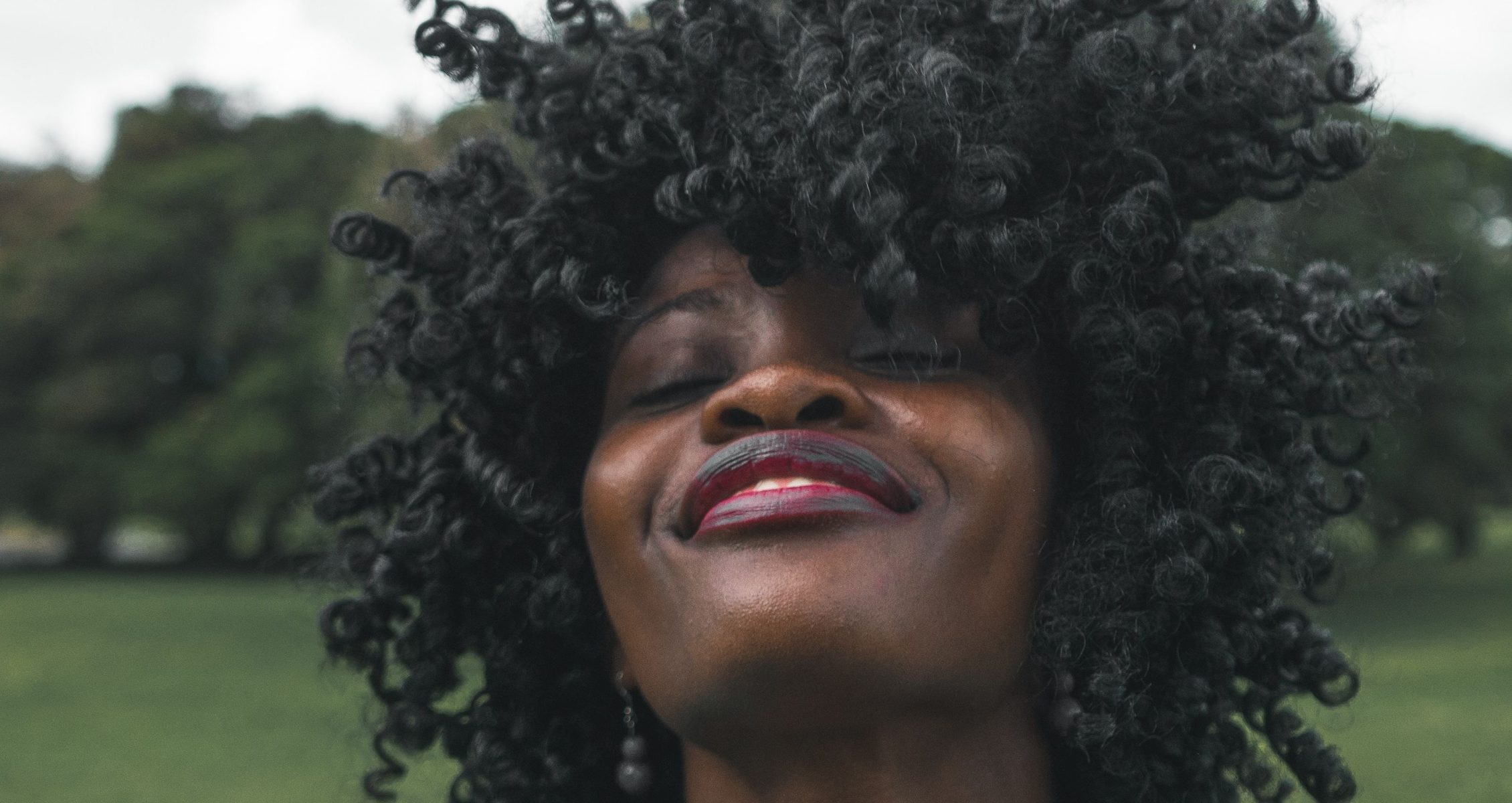 Woman with very dark, curly hair smiling up with her eyes closed
