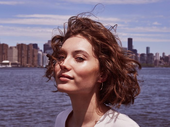 Prose model with short, brown hair posing in from of water and cityscape