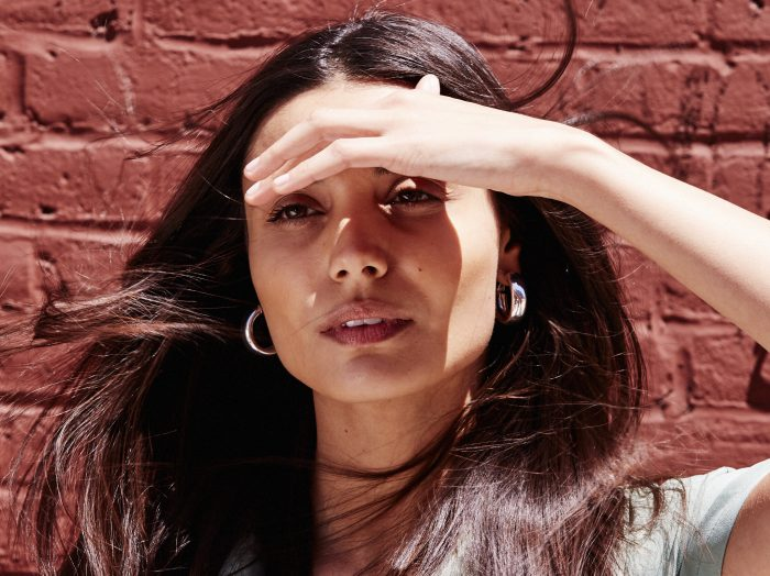 Prose model with straight, dark hair against a brick backdrop shading her eyes from the sun