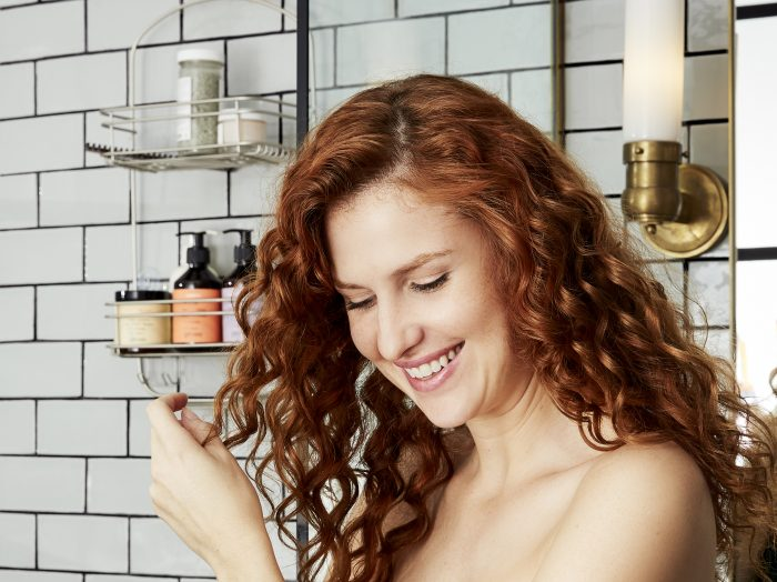 Prose model with curly, red hair a white tile shower smiling