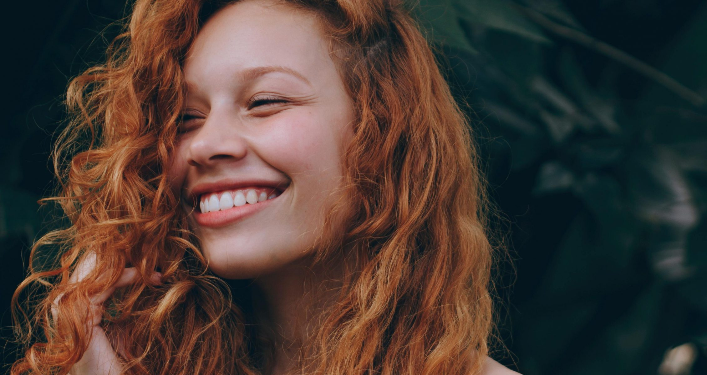 Girl with curly, red hair smiling against greenery