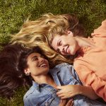 Prose models with long brown and blonde hair laugh while laying in grass