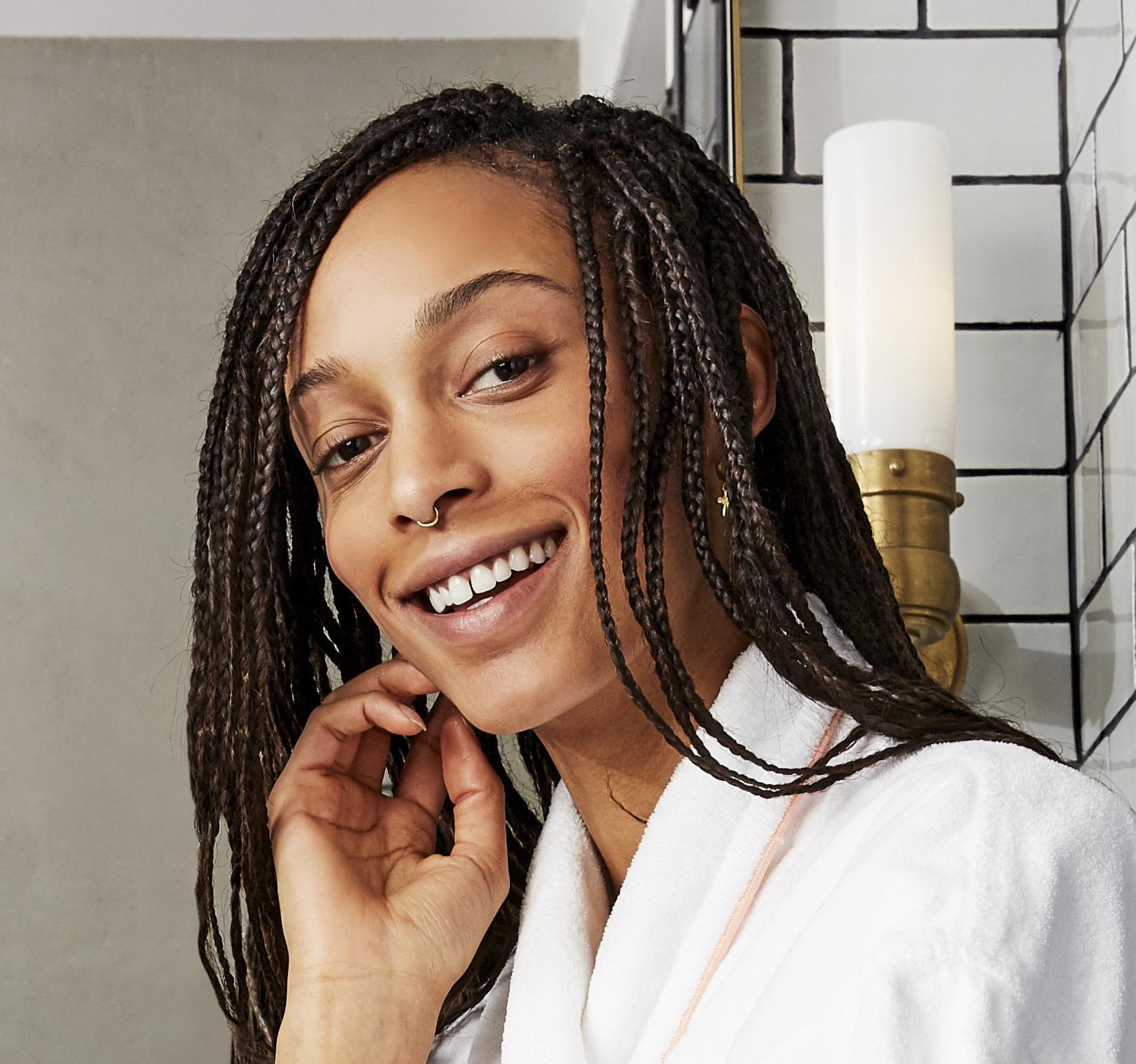 Prose model with braids posing in a bathrobe in a bathroom