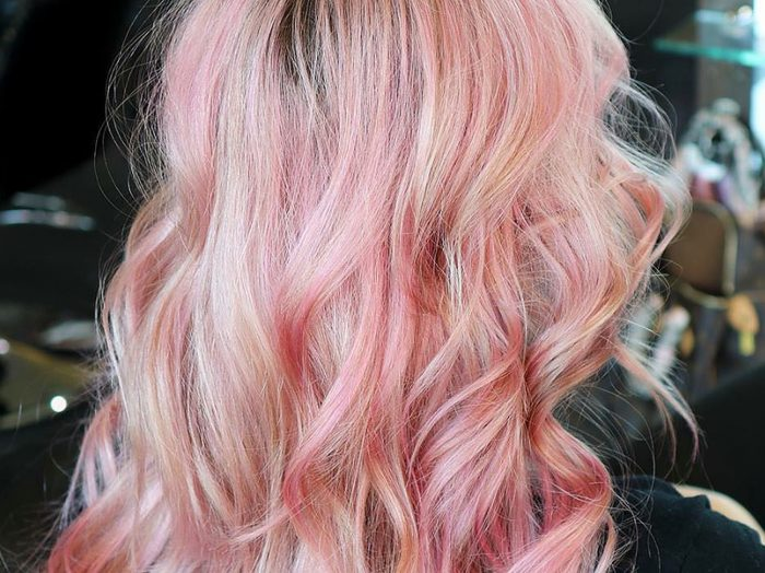 woman with pink hair that's been curled at a salon