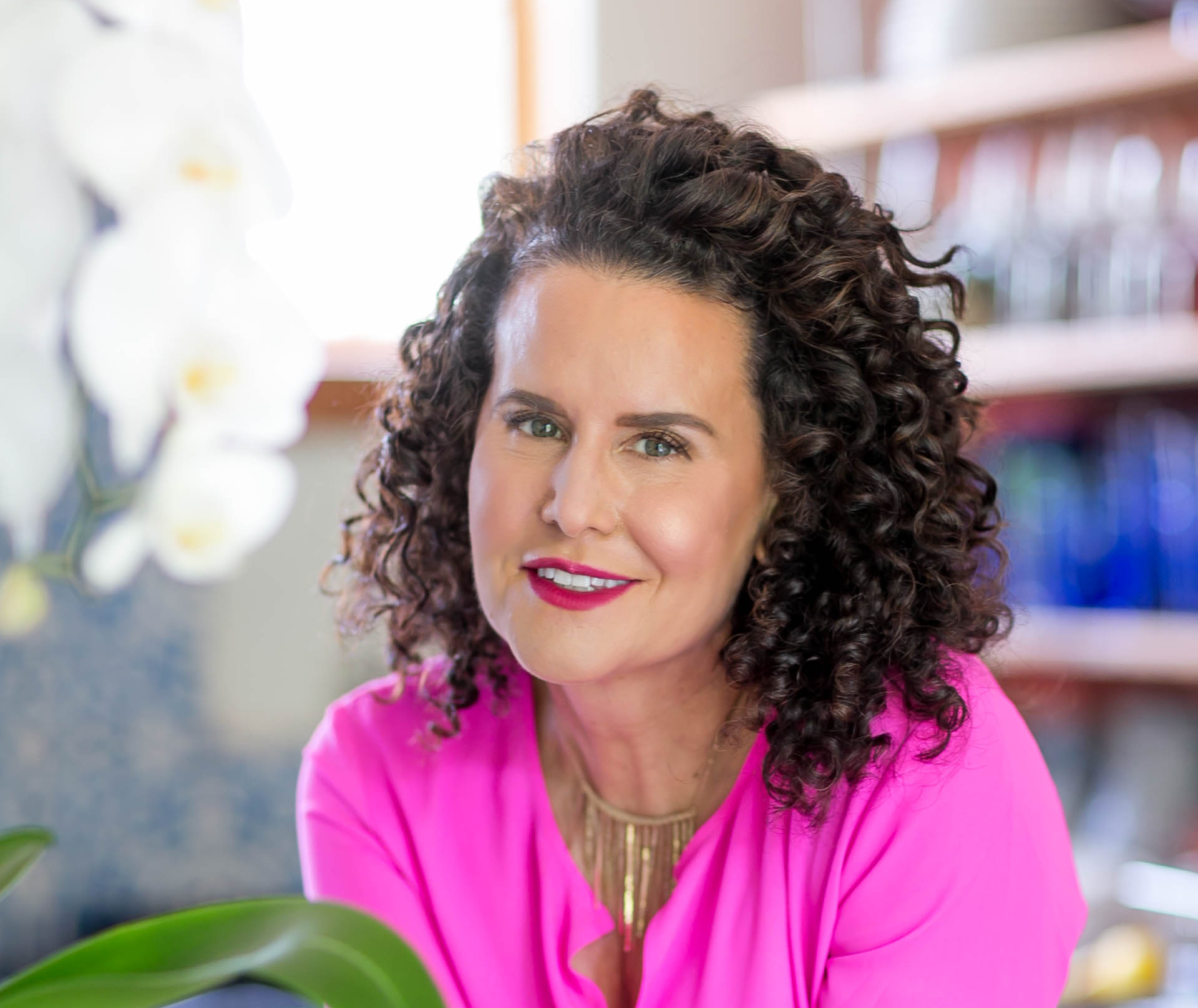 naturally curly founder michelle breyer poses with her dark, curly hair in a hot pink top
