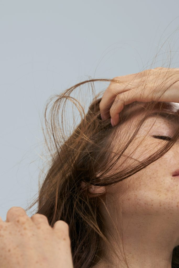 woman with auburn hair and a freckled complexion runs her fingers through her hair as a gust of wind blows her strands