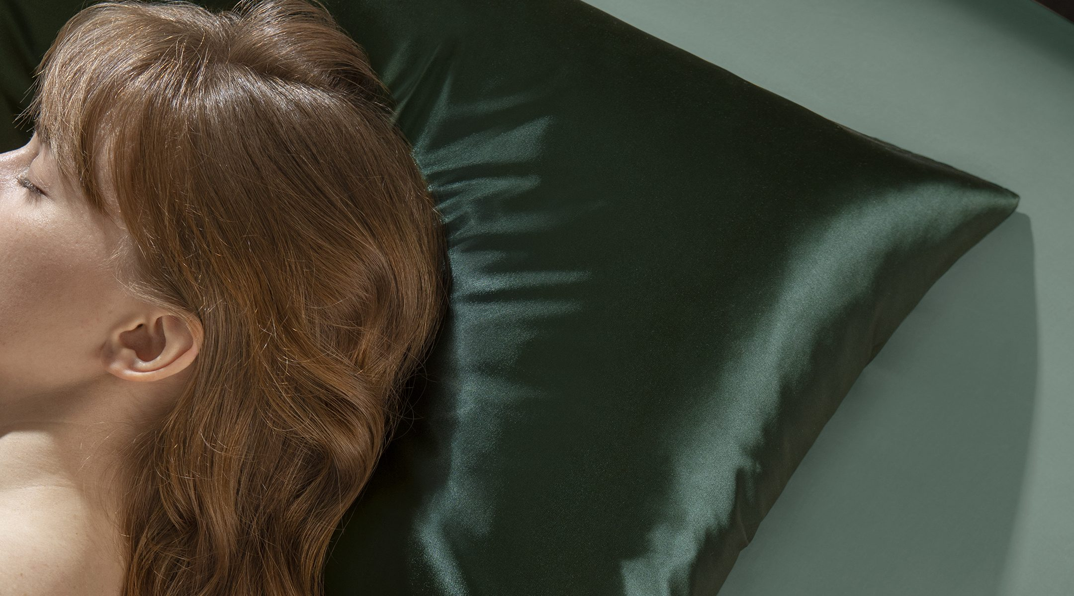 woman with wavy brown hair and bangs sleeping on a dark green silk pillowcase