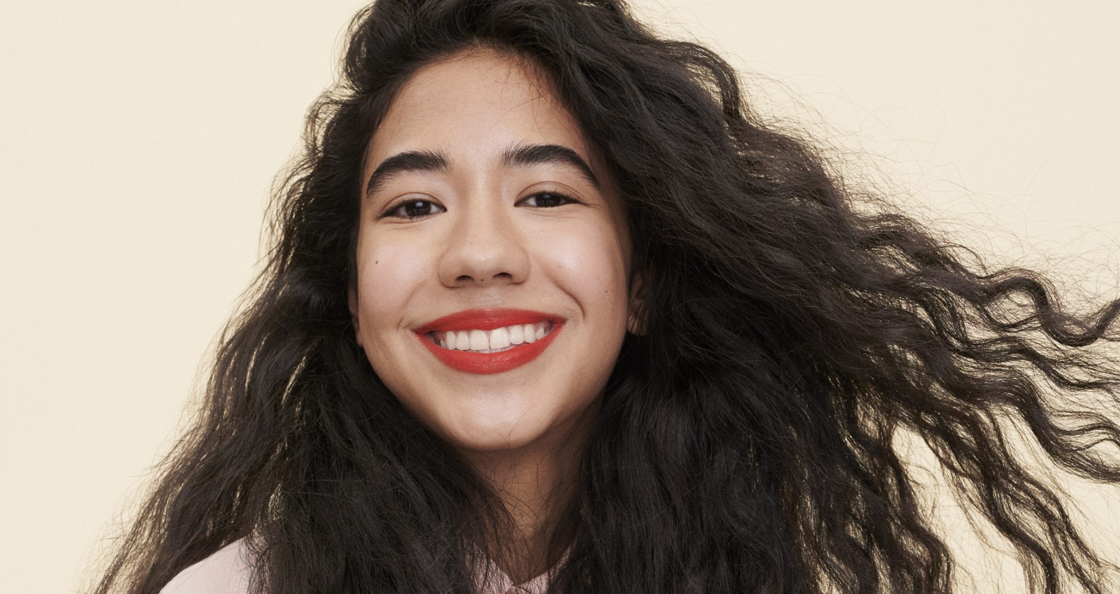 girl with long, black wavy hair smiles at the camera while wearing red lipstick