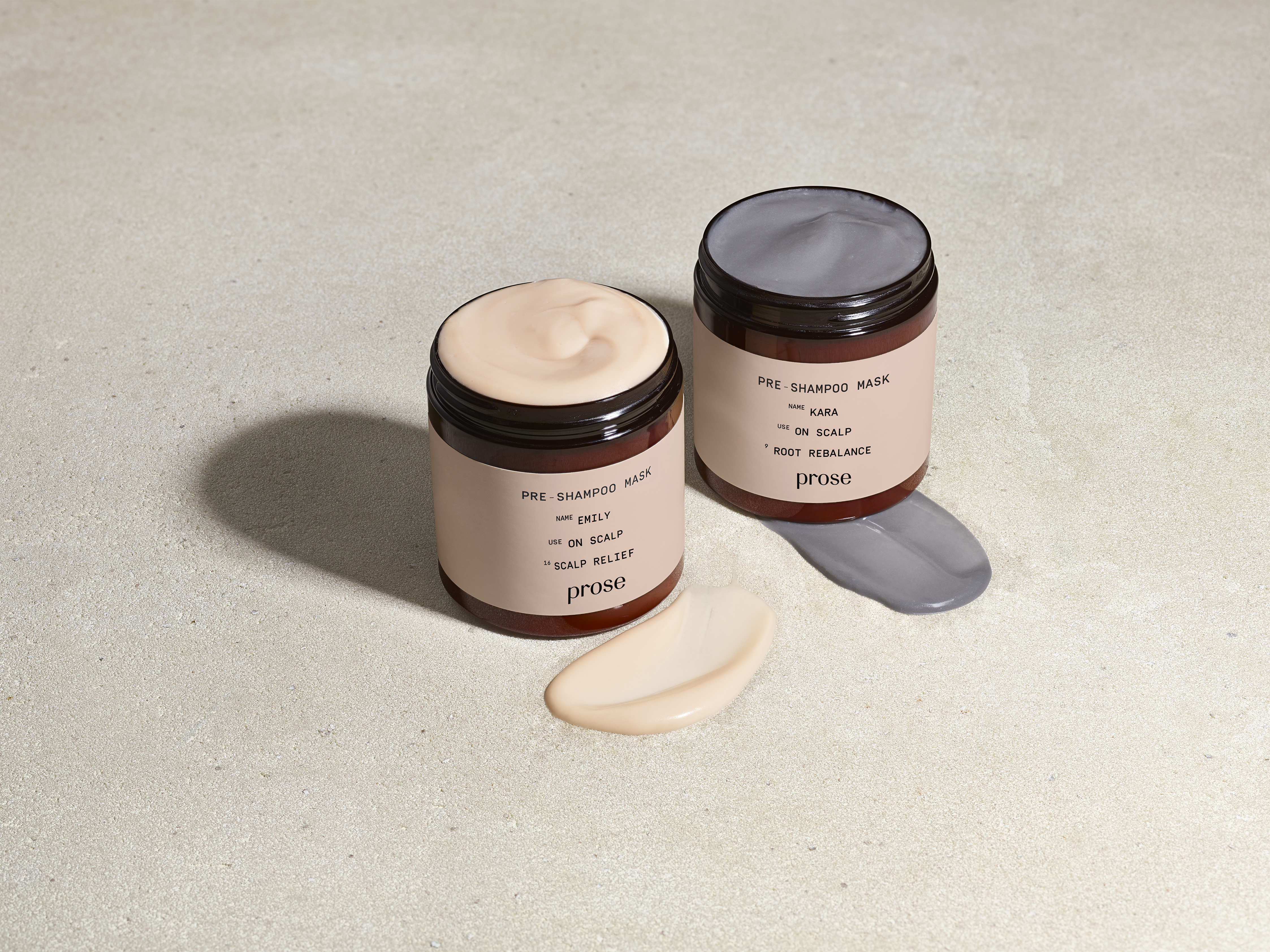 the Prose charcoal and grapefruit scalp mask sit next to each other with their lids open
