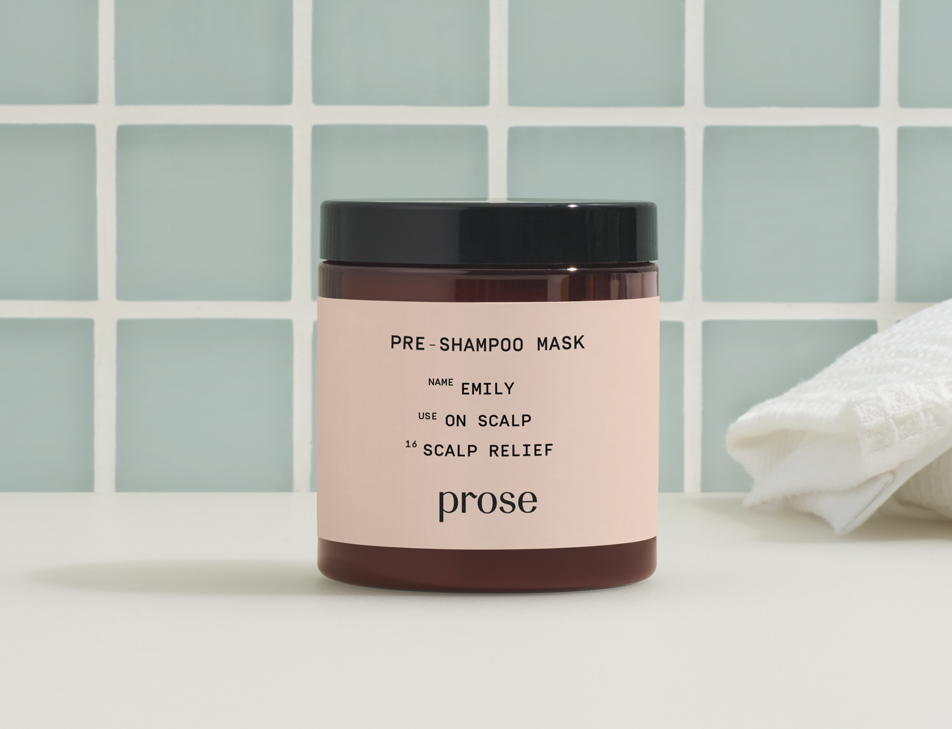 prose scalp mask sits on a bathroom counter with sea foam green tile in the background