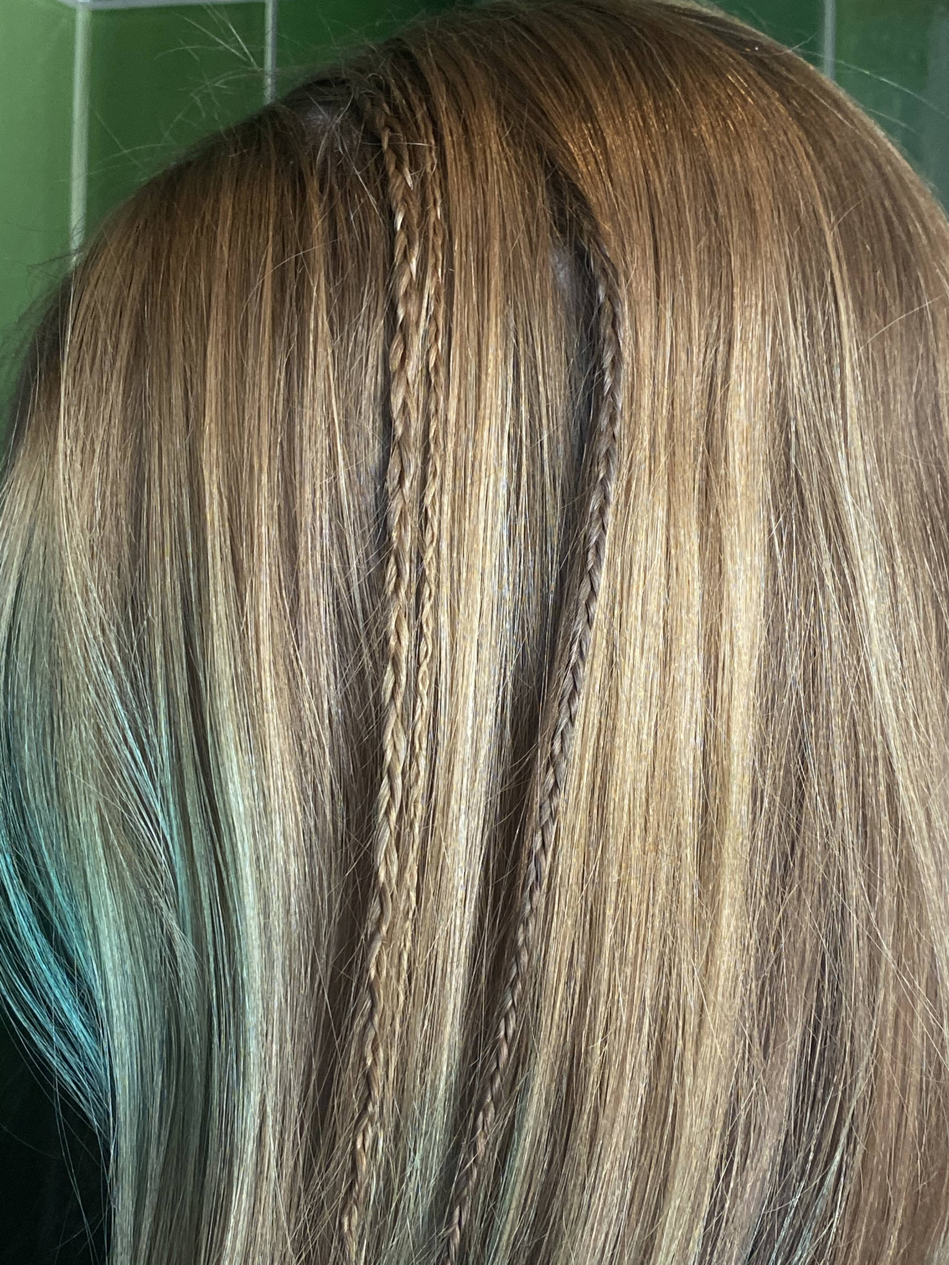 girl with straight blonde hair and blue tips poses with tiny braids in her hair