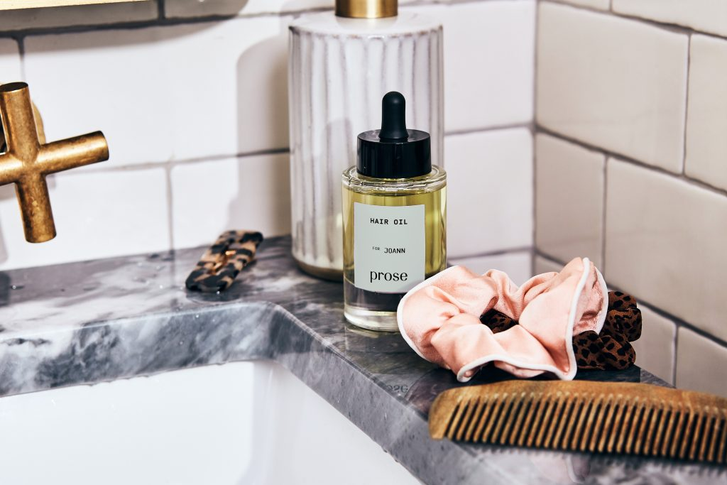 prose custom hair oil sits on a marble sink