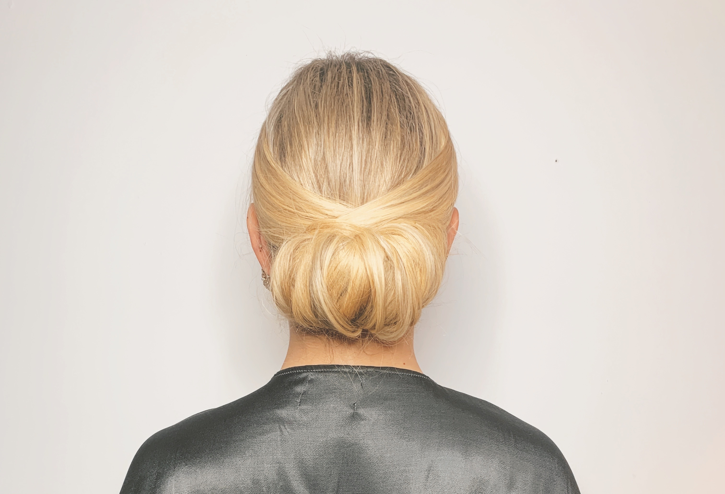 woman wearing a green, silk robe with her blonde hair in a chignon