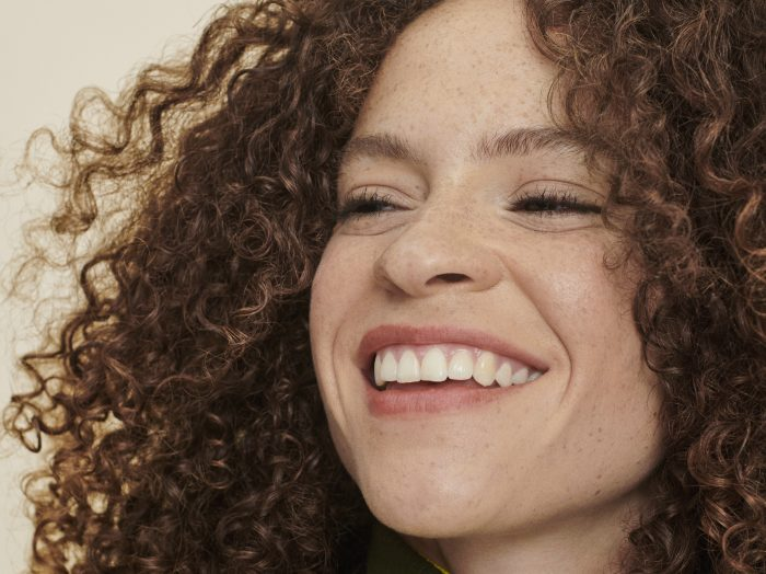 woman with brown, curly hair smiles