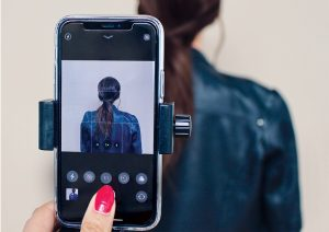 woman takes a photo of a woman with brown hair with an iphone