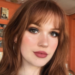 woman with straight, red hair and bangs smiles