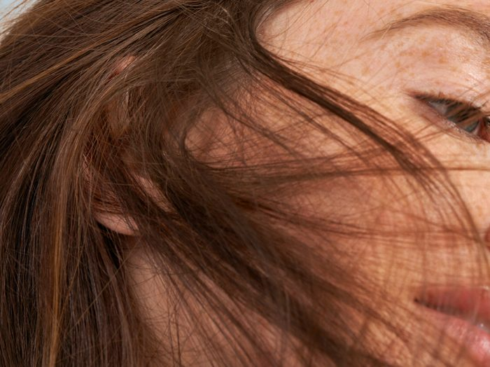 close up portrait of woman with freckles and auburn hair