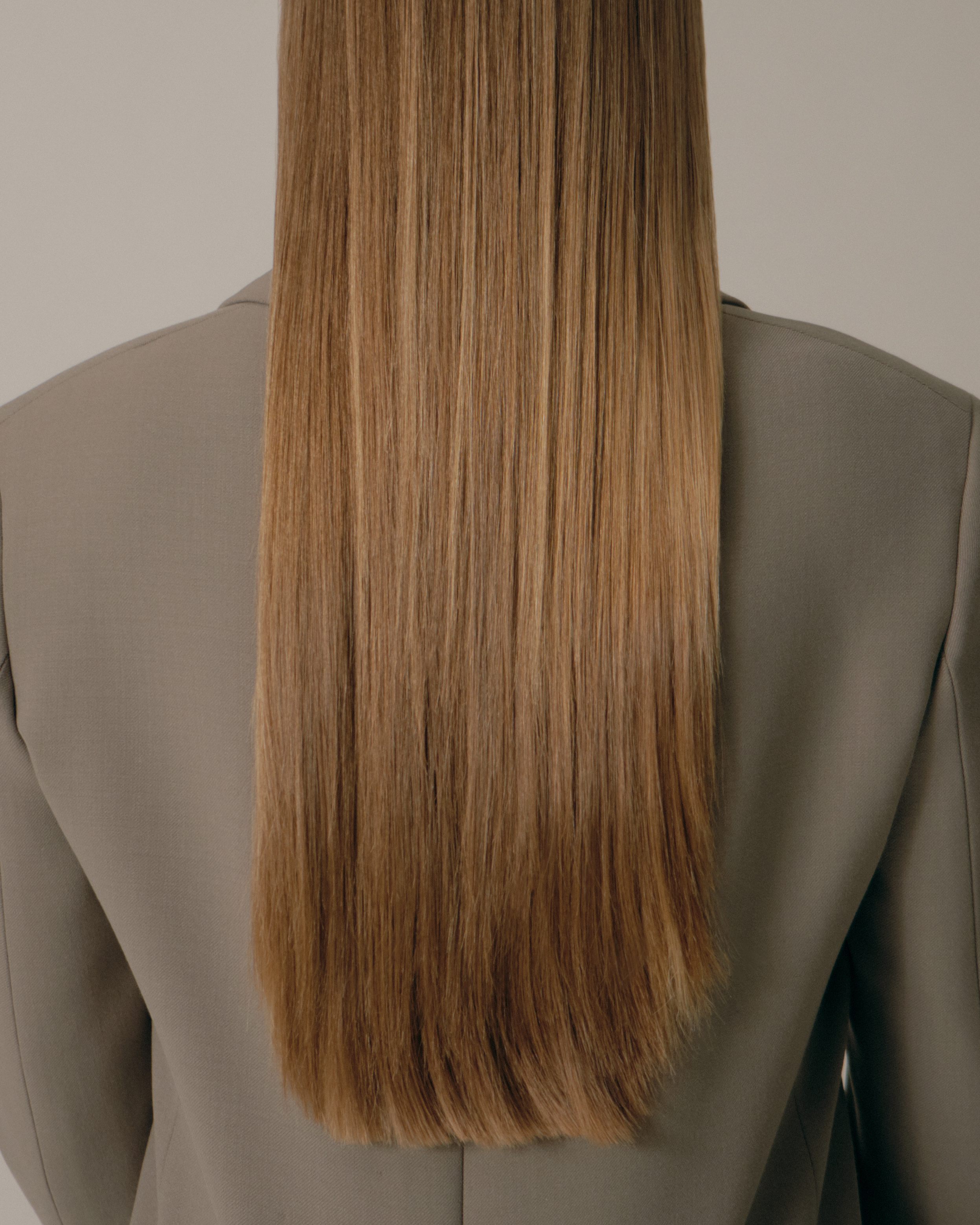 woman with long, straight brown hair has her back to the camera