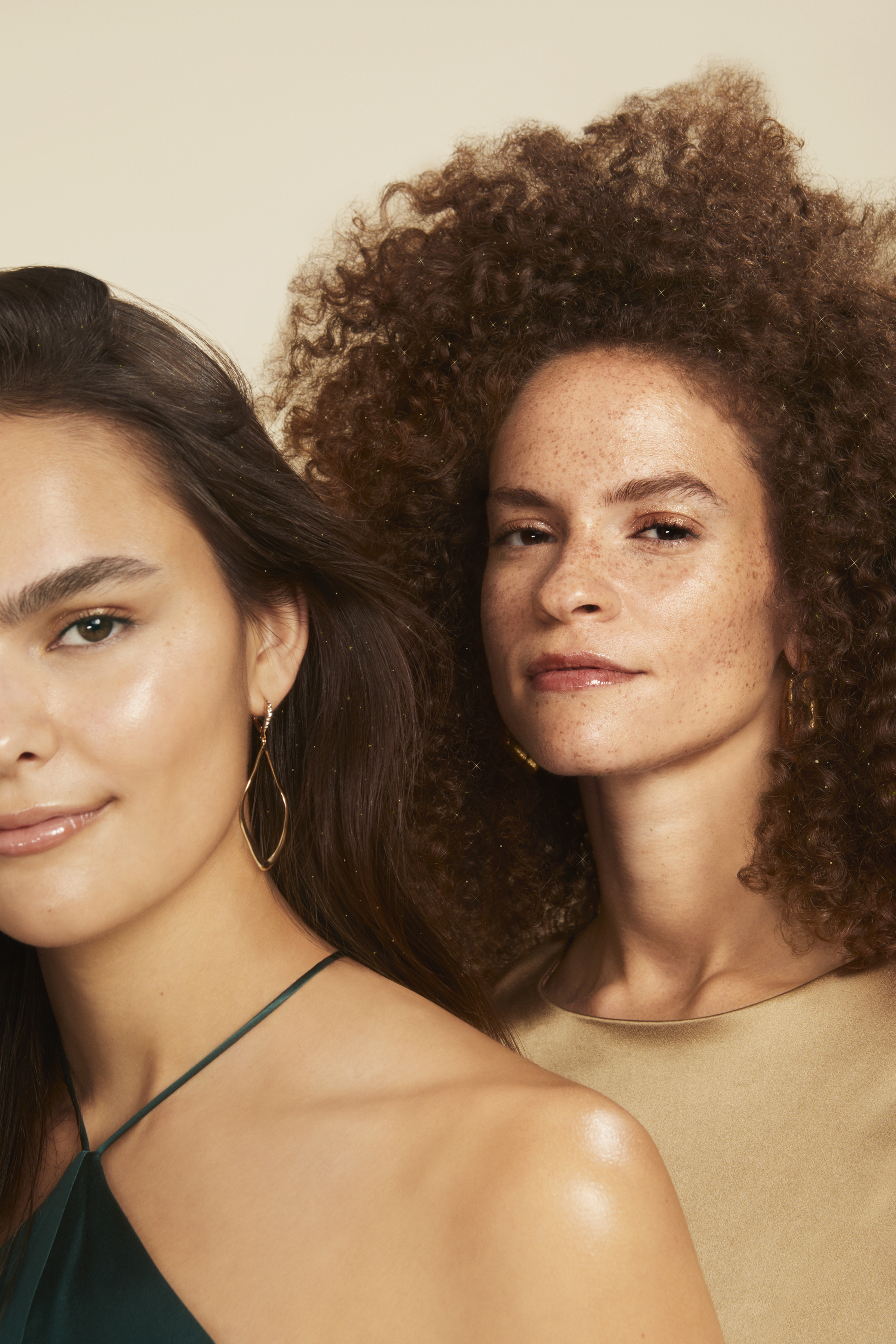 woman with straight brown hair and woman with brown curly hair stand next to each other