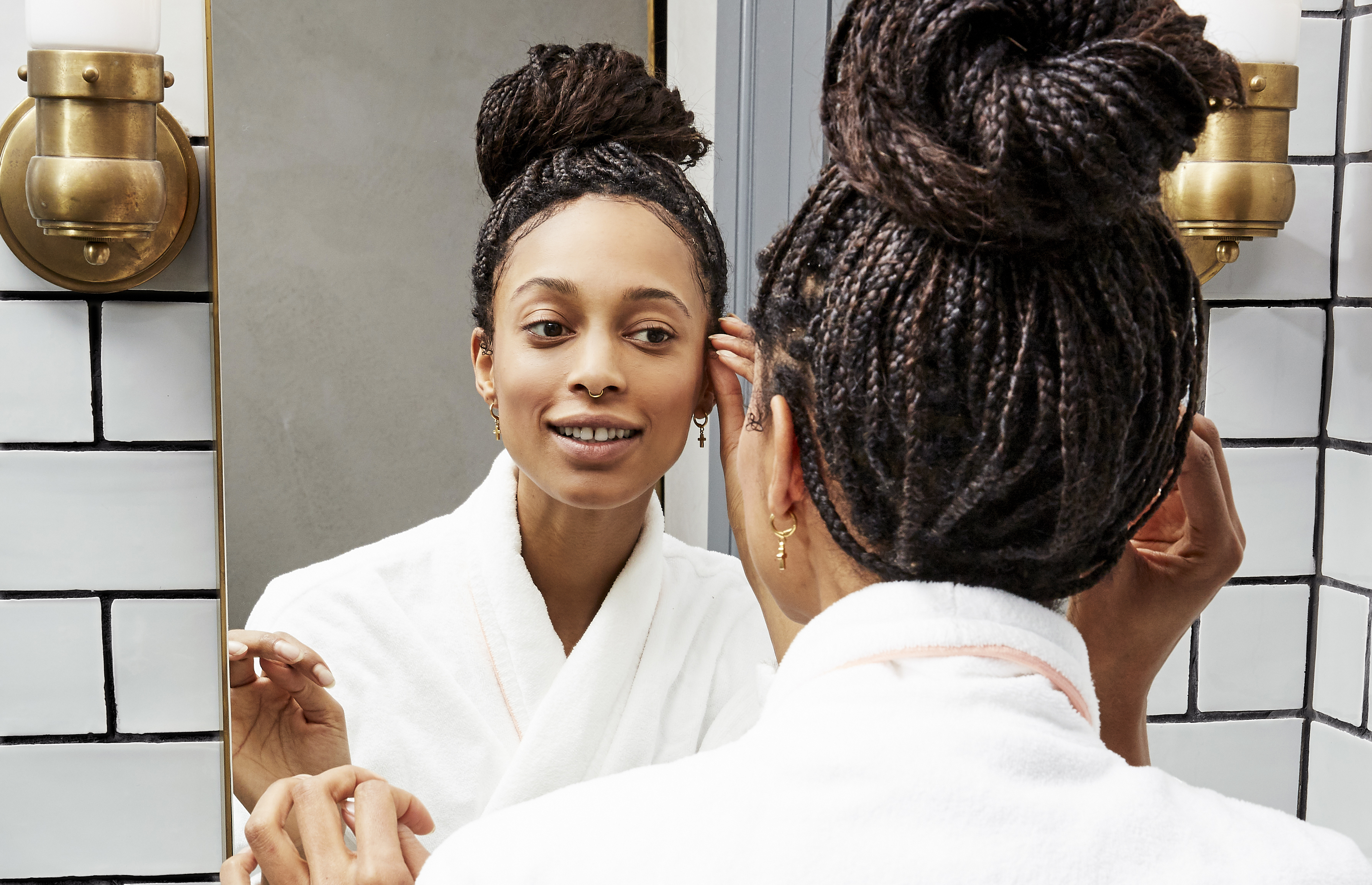 woman with braids smiles into her bathroom mirror