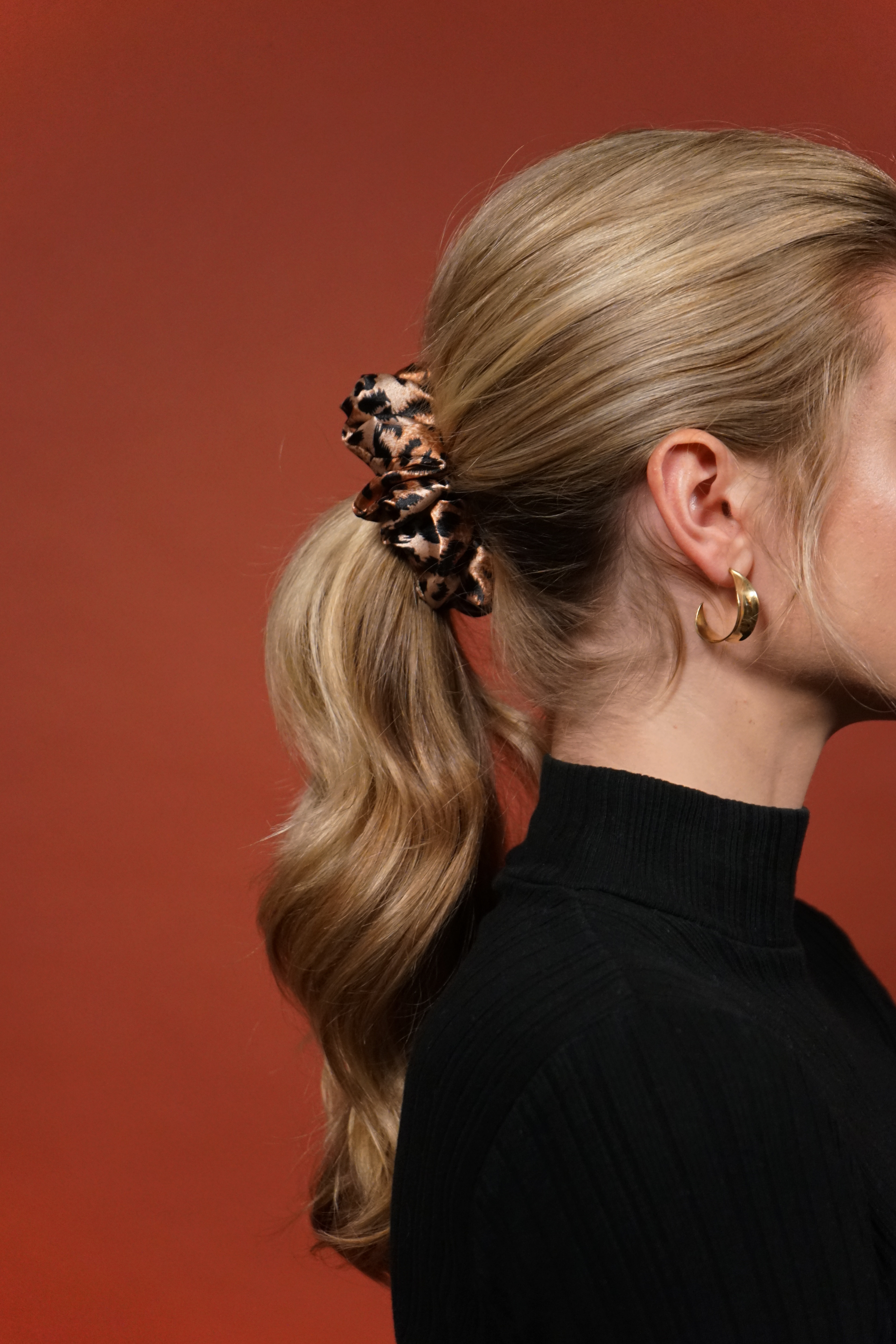 woman with long, blonde hair pulled up in a cheetah scrunchie