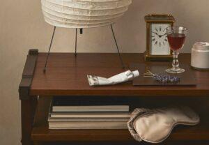 nightstand with eye mask, night cream, clock, and lamp